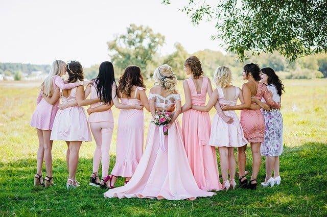 De oplossing voor de kleding van je bruiloftsgasten: spinning closet - bruid met bruidsmeisjes in verschillende roze kleding